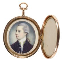 AN OVAL GILT-METAL LOCKET | <em> </em>