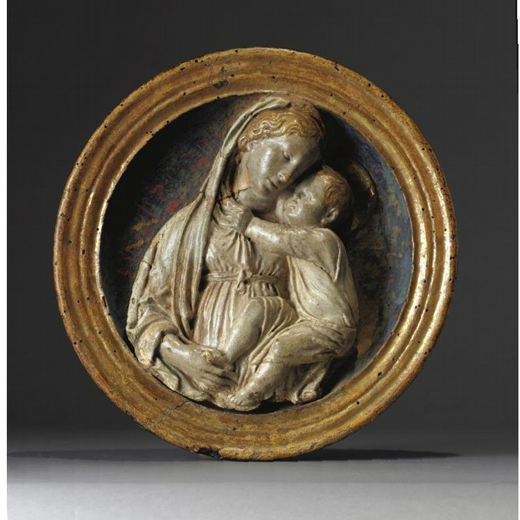A RARE ITALIAN GILT AND PAINTED TERRACOTTA AND WOOD TONDO OF THE MADONNA AND CHILD, BY LUCA DELLA ROBBIA (1399-1482), CIRCA 1440, FLORENCE