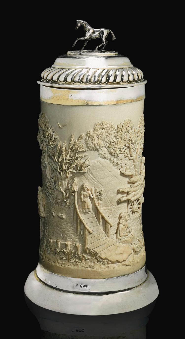 A TALL CARVED IVORY CUP WITH PARCEL-GILT SILVER MOUNTS AND COVER, CHARLES EDWARDS, LONDON, 1889 | A tall carved ivory cup with parcel-gilt silver mounts and cover, Charles Edwards, London, 1889