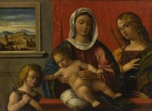 CIRCLE OF GIOVANNI BELLINI | The Madonna and Child with the Infant Saint John the Baptist and Saint Catherine of Alexandria behind a ledge, a window onto a landscape in the background