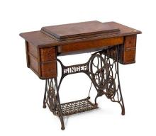 A Singer treadle-based sewing machine, circa 1910 76 cm high, 93 cm long, 35 cm depthAccompanied by a letter from Russell Crowe stat...