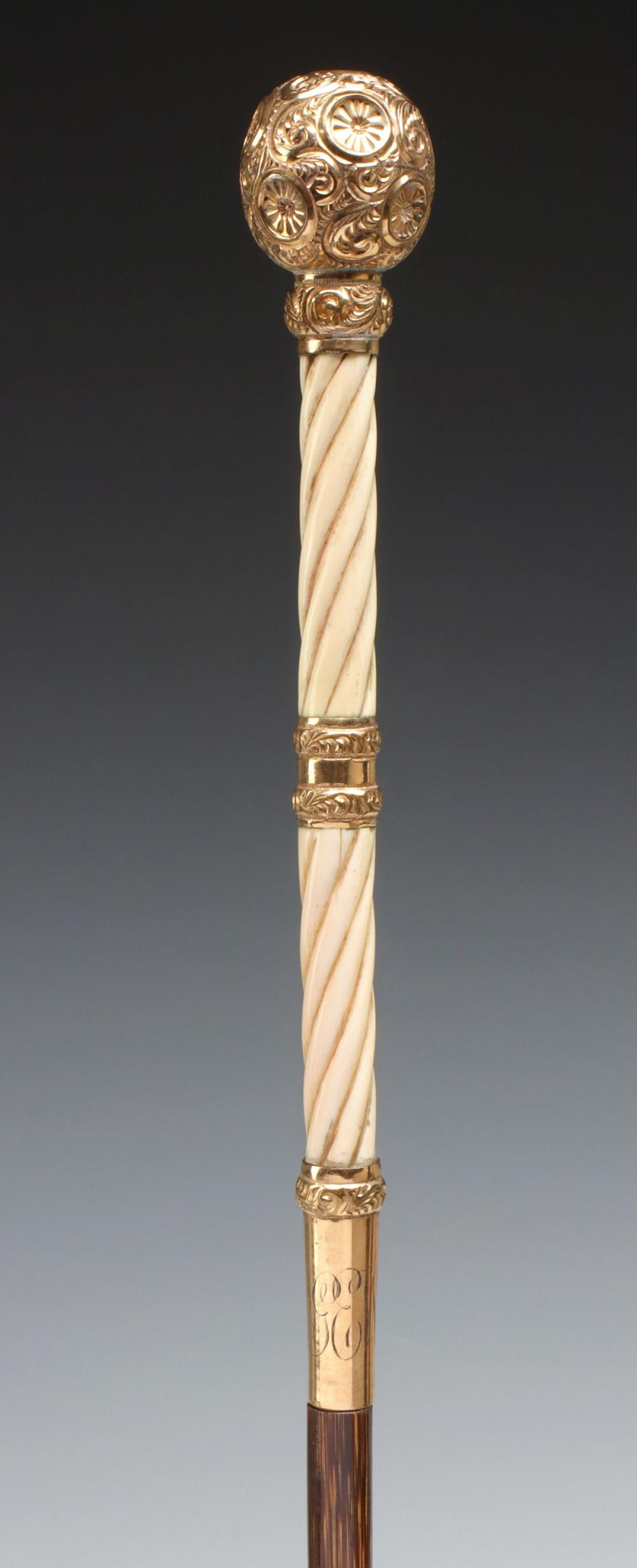 A GOLD FILLED, IVORY AND PARTRIDGE WOOD DAGGER CANE
