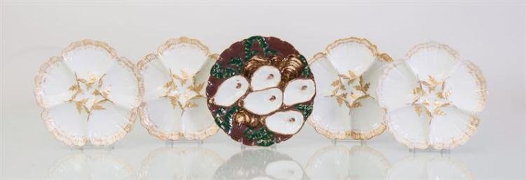 SET OF FOUR LIMOGES PORCELAIN GILT AND WHITE GLAZED OYSTER PLATES AND A BROWN GROUND OYSTER PLATE