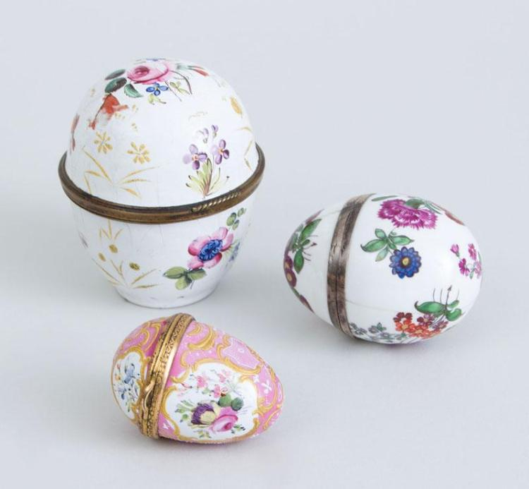 TWO SOUTH STAFFORDSHIRE ENAMEL EGG-FORM BOXES AND A PORCELAIN EGG-FORM BOX
