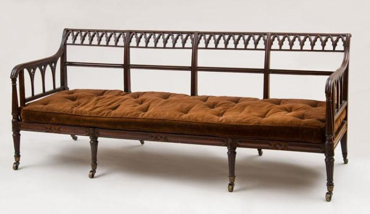 WILLIAM IV CARVED MAHOGANY AND CANED SETTEE, IN THE NEO-GOTHIC TASTE