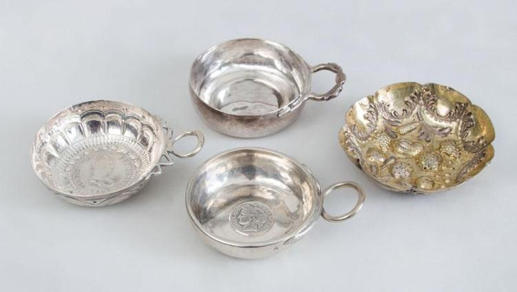 SPANISH COIN-MOUNTED SILVER WINE TASTER, A FRENCH COIN-MOUNTED SILVER TASTER, UNEMBELLISHED TASTER AND A GOLD-WASH TASTER