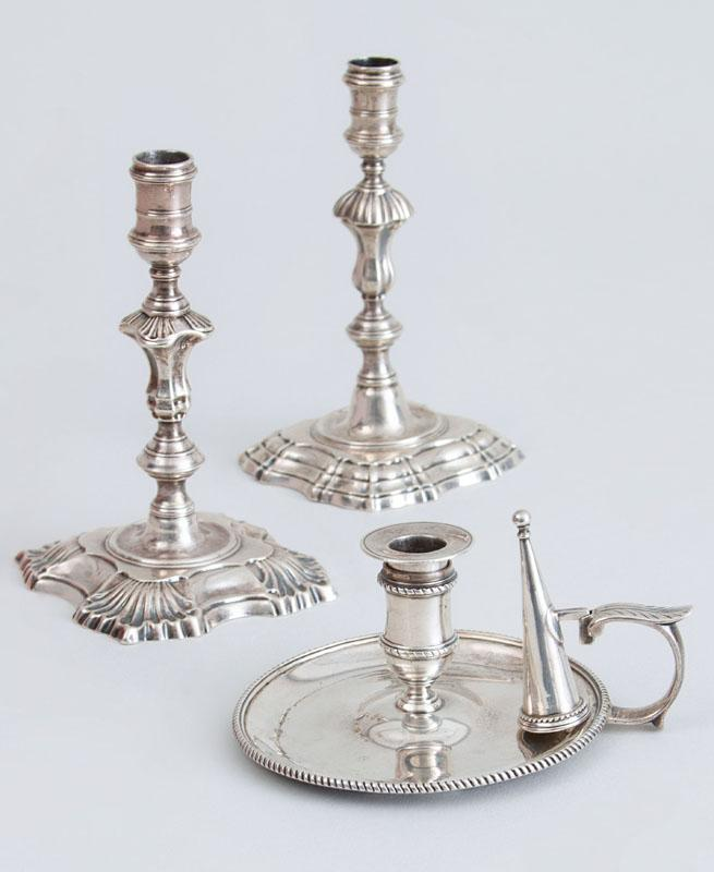 TWO SIMILAR GEORGE II CRESTED SILVER TAPER CANDLESTICKS AND A GEORGE III SILVER CHAMBER CANDLESTICK WITH ASSOCIATED FUNNEL SNUFFER