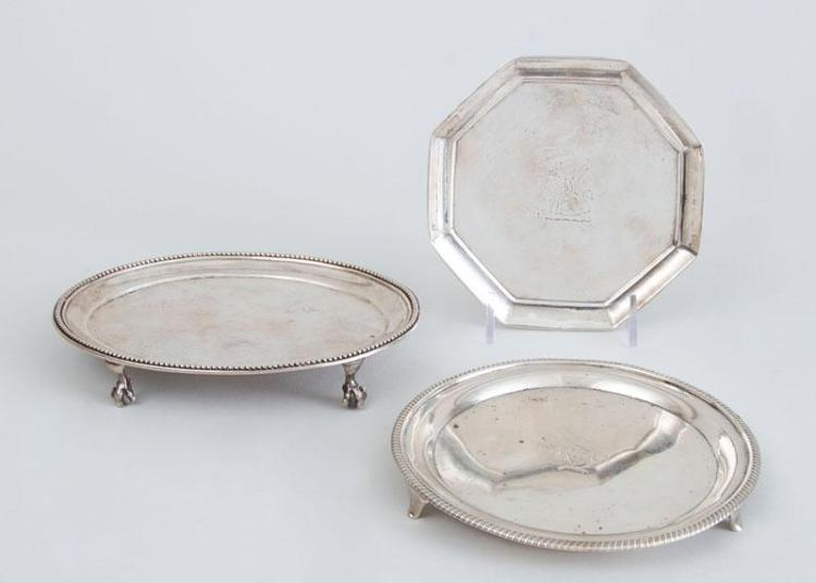 TWO GEORGE III SILVER TEAPOT STANDS AND A GEORGE III CRESTED OCTAGONAL SMALL TRAY