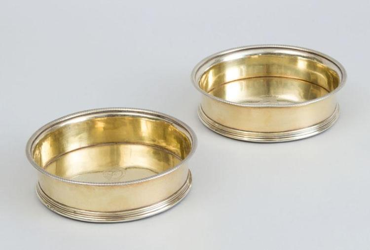 PAIR OF GEORGE III CRESTED SILVER-GILT BOTTLE COASTERS