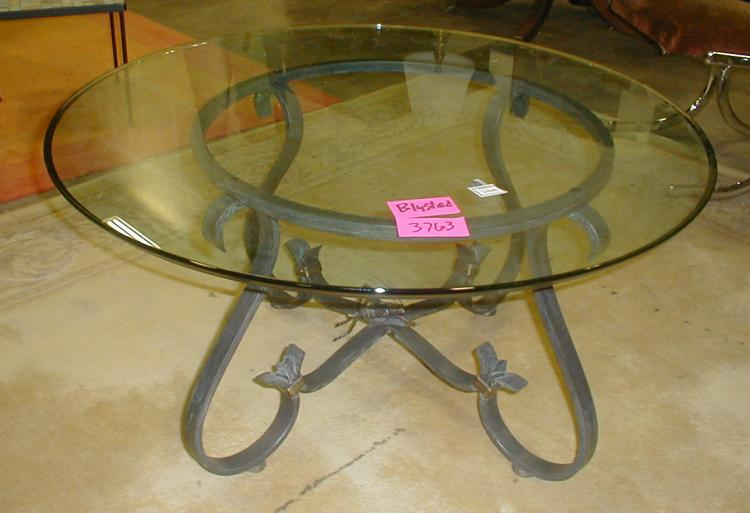 Round glass top coffee table on wrought iron base with central grass hopper  finial