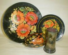 Russian wooden lacquer ware: two plates, egg, and pencil cup. Largest plate is 11