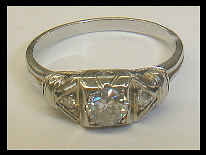 Deco lady's 18k white gold & diamond ring. The center stone is approximately VS and is 4.6mm wide(0.38cts). The two smaller side diamonds are chipped. Size 6 1/2. weight 2.3 grams.