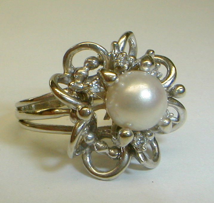 Ladies 14k white gold ring with 8mm central pearl and five single cut diamonds. One arm for a diamond is missing. See photos. Size 8. Total weight 8.0 grams