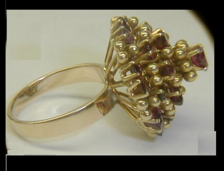 Ladies 18k yellow gold cocktail ring with garnets. Size 8 1/2. Total weight 12.3 grams. Has imperfect 18k mark tested 18k.