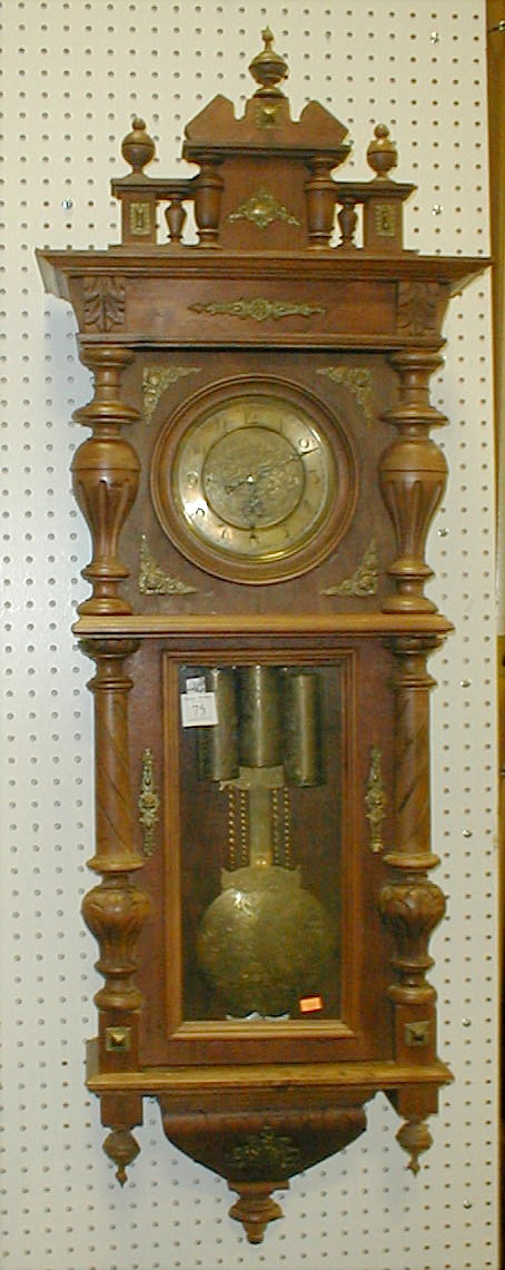 German Vienna regulator wall clock in an Alt Deutsch style walnut case. Three weights. Turned brass face. Unsigned. 4'5