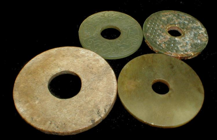 Four Chinese jade bi's. Archaic brown, rice pattern, Tao Tich carved and green. Largest is 2.75