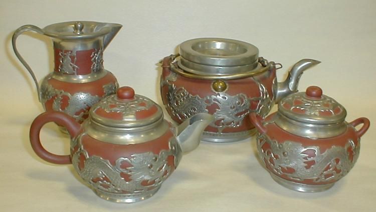 Chinese Four Piece Pewter- Mounted Clay Tea Set with Dragon Decoration. Lid on teapot has coin, all pieces are marked (see photos). Tallest piece is 5.5