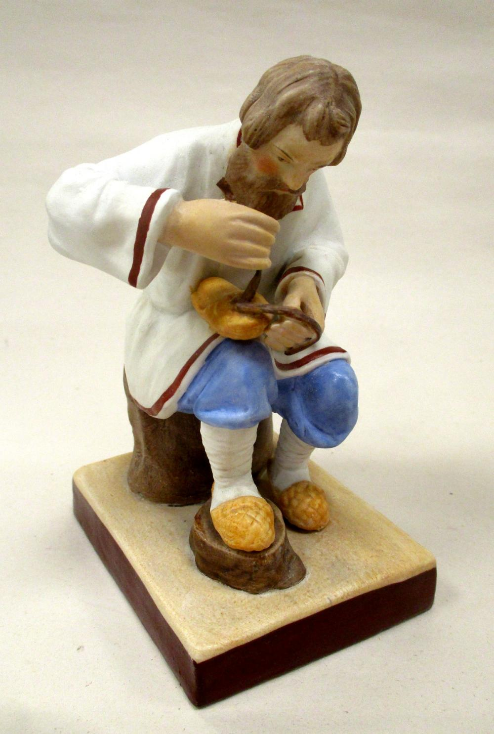 """A RUSSIAN PORCELAIN FIGURE OF A BAST SHOE MAKER BY GARDNER. IMPRESSED MARK AND INK STAMP. 5"""" TALL"""