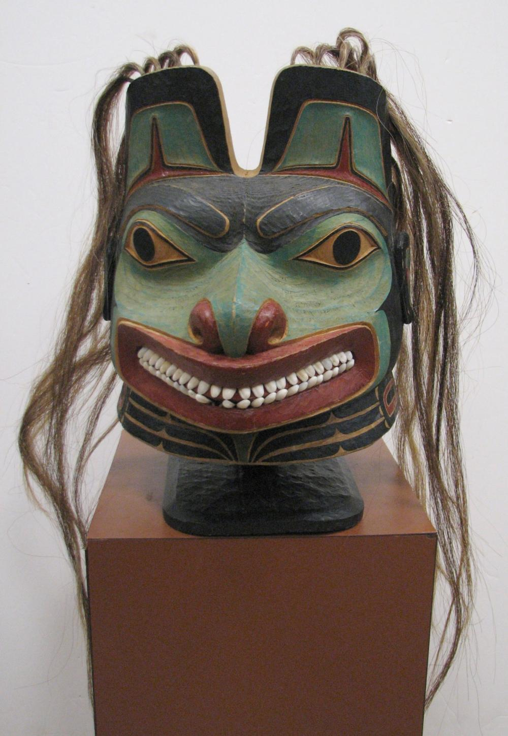 """RICHARD A. BROWN NORTHWEST NATIVE AMERICAN STYLE TLINGIT HELMET. A COMMISSIONED WORK, SIGNED AND DATED 2011. THE MASK IS 12"""" TALL EXCLUDING THE HAIR AND STAND. 15.5"""" WIDE. MADE OF CEDAR, HORSE TAIL HAIR AND SHELL TEETH"""