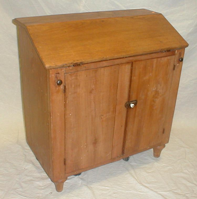 Primitive drop front school desk with lower cupboard. Constructed of solid wood planks. 32.75