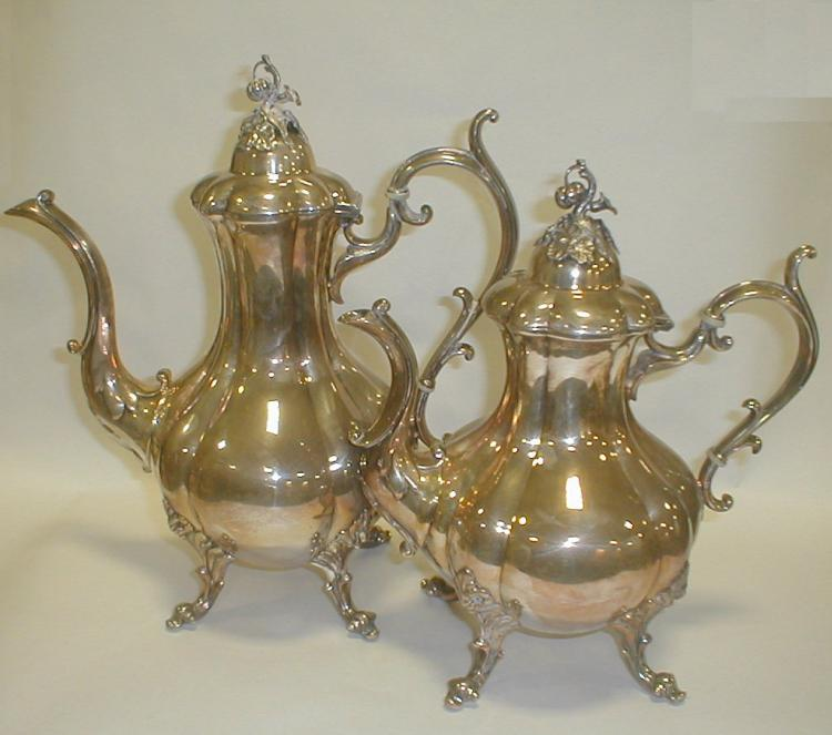 Two contemporary Reed & Barton silver plated coffee pots. Neither stands level.