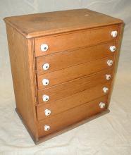Primitive oak spool cabinet with porcelain pulls. Stencil on back reads