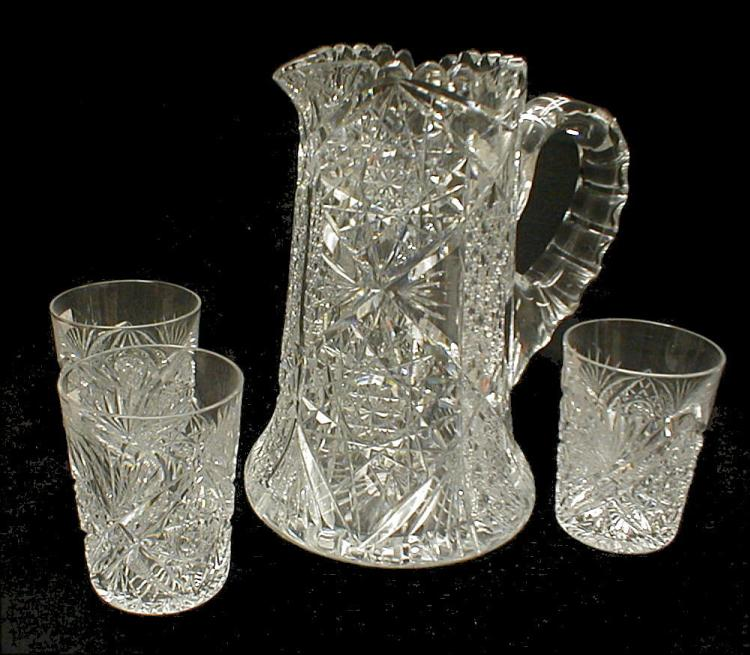 Cut glass pitcher and three tumblers. Pitcher is 9