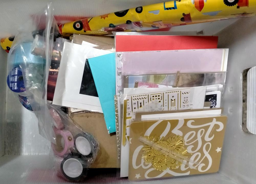 A box of assorted gift cards, gift wrap & ribbon
