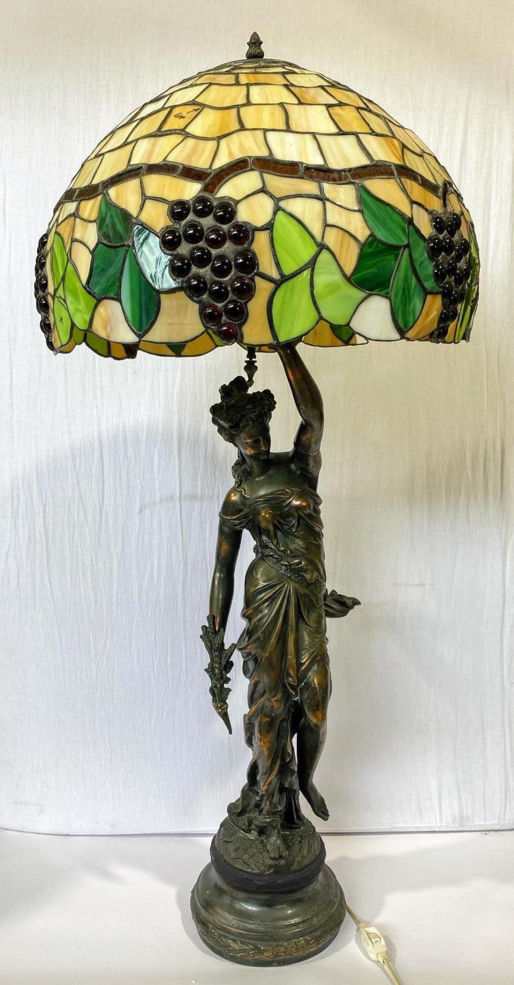 An Impressive Table Lamp of a Classical figure in spelter supporting a Tiffany Style Glass shade (shade damaged in a fall)
