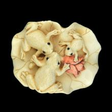 A JAPANESE CARVED IVORY NETSUKE OF THREE FROGS ON A LEAF