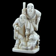 A JAPANESE CARVED IVORY NETSUKE OF THREE FIGURES BY A WELL