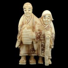 A JAPANESE CARVED IVORY NETSUKE OF A PAIR OF NOMADS