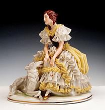 A GERMAN PORCELAIN FIGURE MODELED IN THE FORM OF A GIRL WITH A DOG AT HER FEET