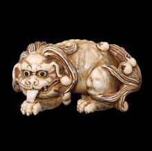 A JAPANESE CARVED IVORY NETSUKE OF A SHISHI LION