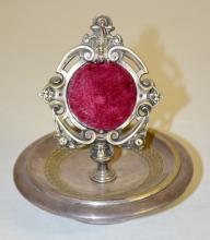 Antique Silver Plate Pocket Watch Holder in the Form of A Devil's Mask: There is a round base with a ripple-like decoration. The center stand holds the pocket watch and has an ornate border with a devil mask at the top.