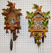 2 German Carved and Painted Cuckoo Clocks: The larger has 2 birds and leaves, the pendulum and 2 weights. The smaller one has 3 birds and a nest, the pendulum and 2 weights. Both sell as is, where is.