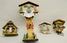 3 Miniature Painted Cuckoo Clocks and Thermometer, Swiss Cottage Style: The largest and medium have a girl on a spring that moves the bird. The smallest has a bird and is marked Germany. The cottage is a thermometer with a man & woman.