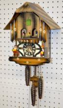 German Painted Cuckoo Clock with Dancing Couple Carousel in Swiss Chalet Form: The movement is marked