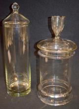 2 Apothecary/Candy Store Jars: 1 is extra tall and slender and has a dome lid. The shorter one has 2 outer rings on the body and a lid with an open finial. Tallest - 16