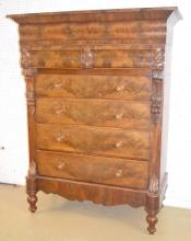 Antique Empire Style Flame Mahogany Highboy Dresser with Hidden Storage: It has 4 large drawers, 2 smaller drawers, a large hidden storage space on the top with a lift top lid. The front has carved fruit and leaves. The drawers have spool handles.