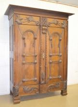 Antique Walnut Ornate Carved French Armoire with Applied Decoration: There are 2 doors and applied decoration of crane like floral figures, other florals, leaves and trim. It also has castle towers with carved card suits at the base of the towers.