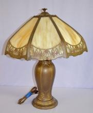 8 Panel Caramel Slag Glass Electric Table Lamp: With 2 light sockets and a molded metal lamp base. The shade frame has an arched church window border with flowers.  Has not been tested. 23