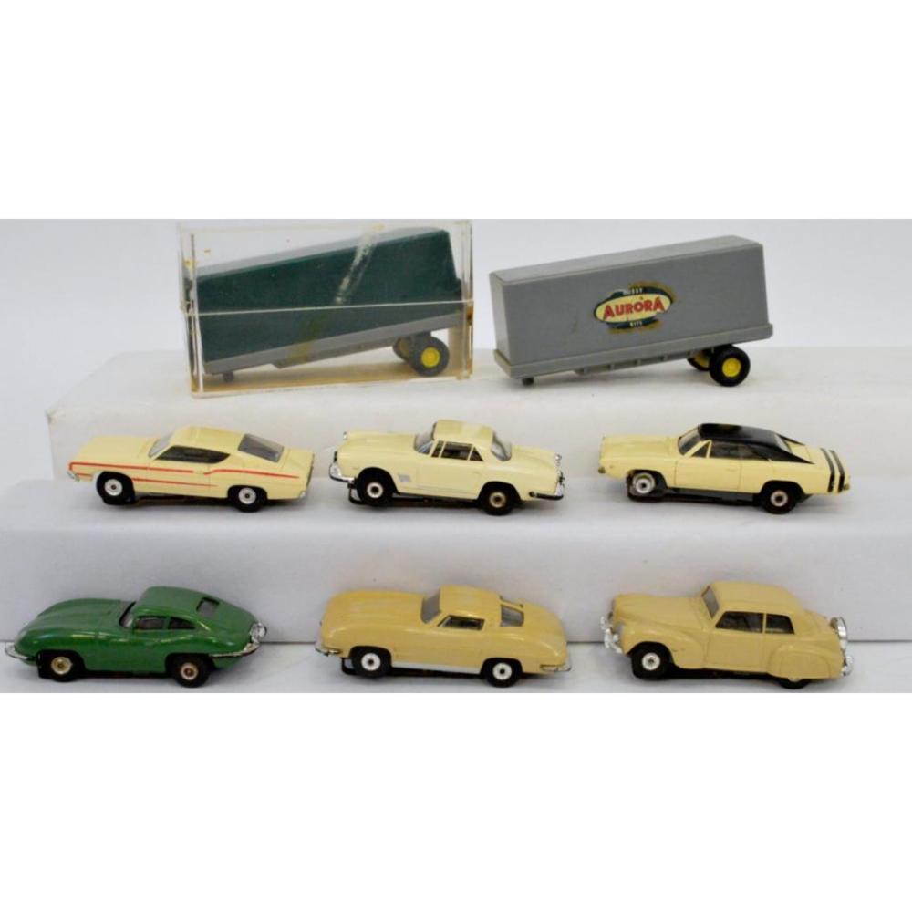 Six Aurora HO slot cars plus two semi trailers, one MIB