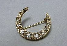 A diamond set crescent brooch Diameter: 2.5cm