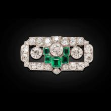 A 1930s emerald and diamond set brooch Length: 38mm, estimated principal diamond weights: 0.67cts, 0.90cts & 0.74cts