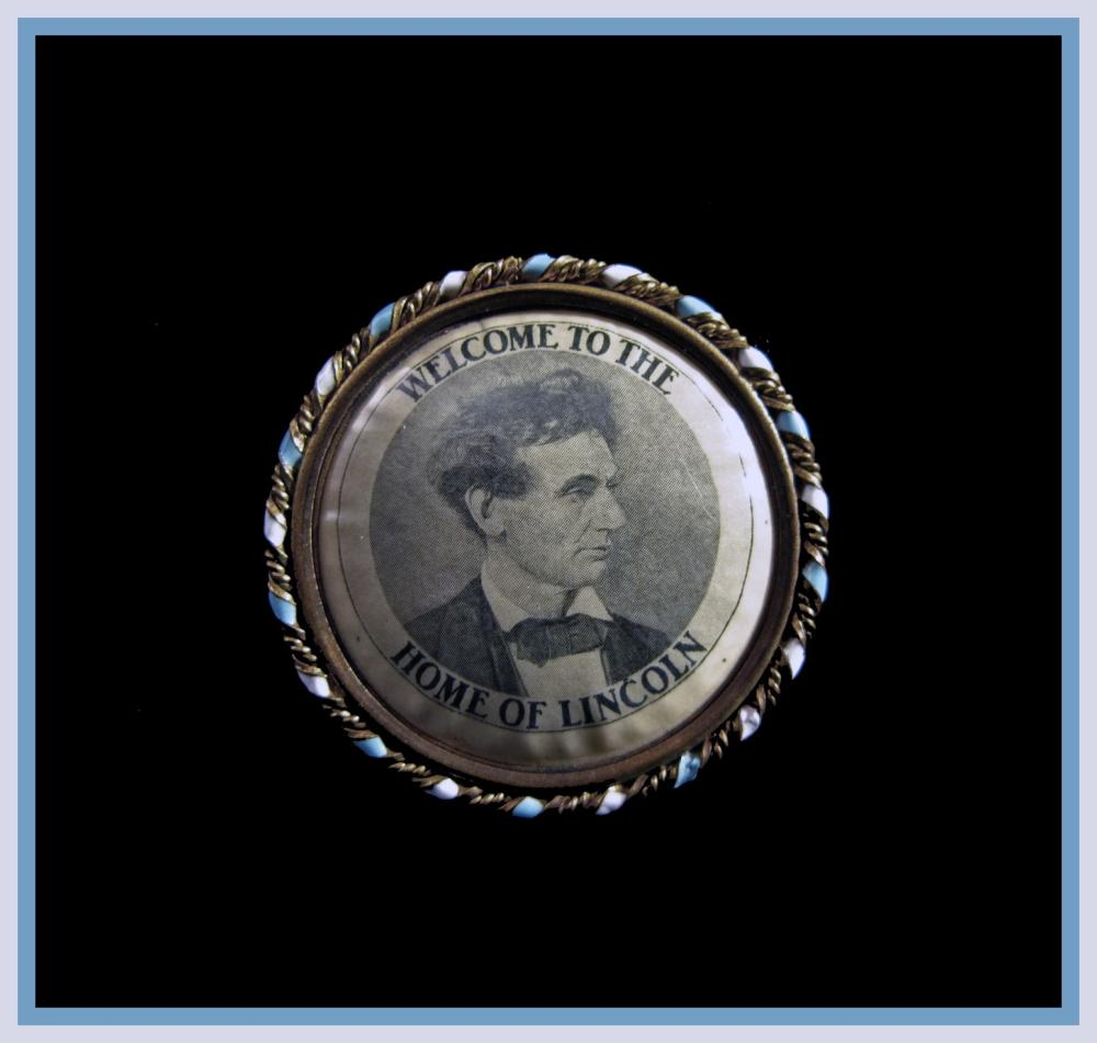 """Attractive pendant displaying Lincoln's beardless """"tousled hair"""" pose on one side, the State Capitol at Springfield on the other"""