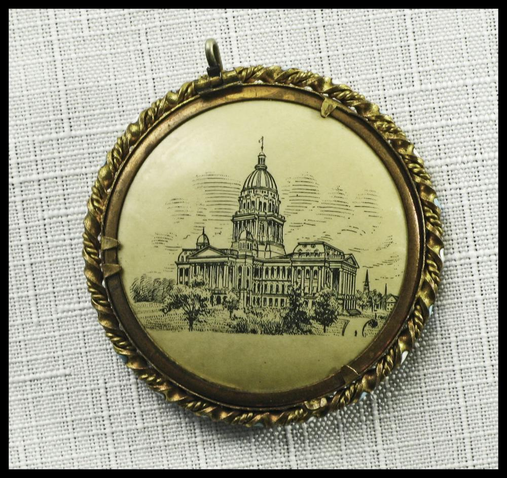 "Attractive pendant displaying Lincoln's beardless ""tousled hair"" pose on one side, the State Capitol at Springfield on the other"