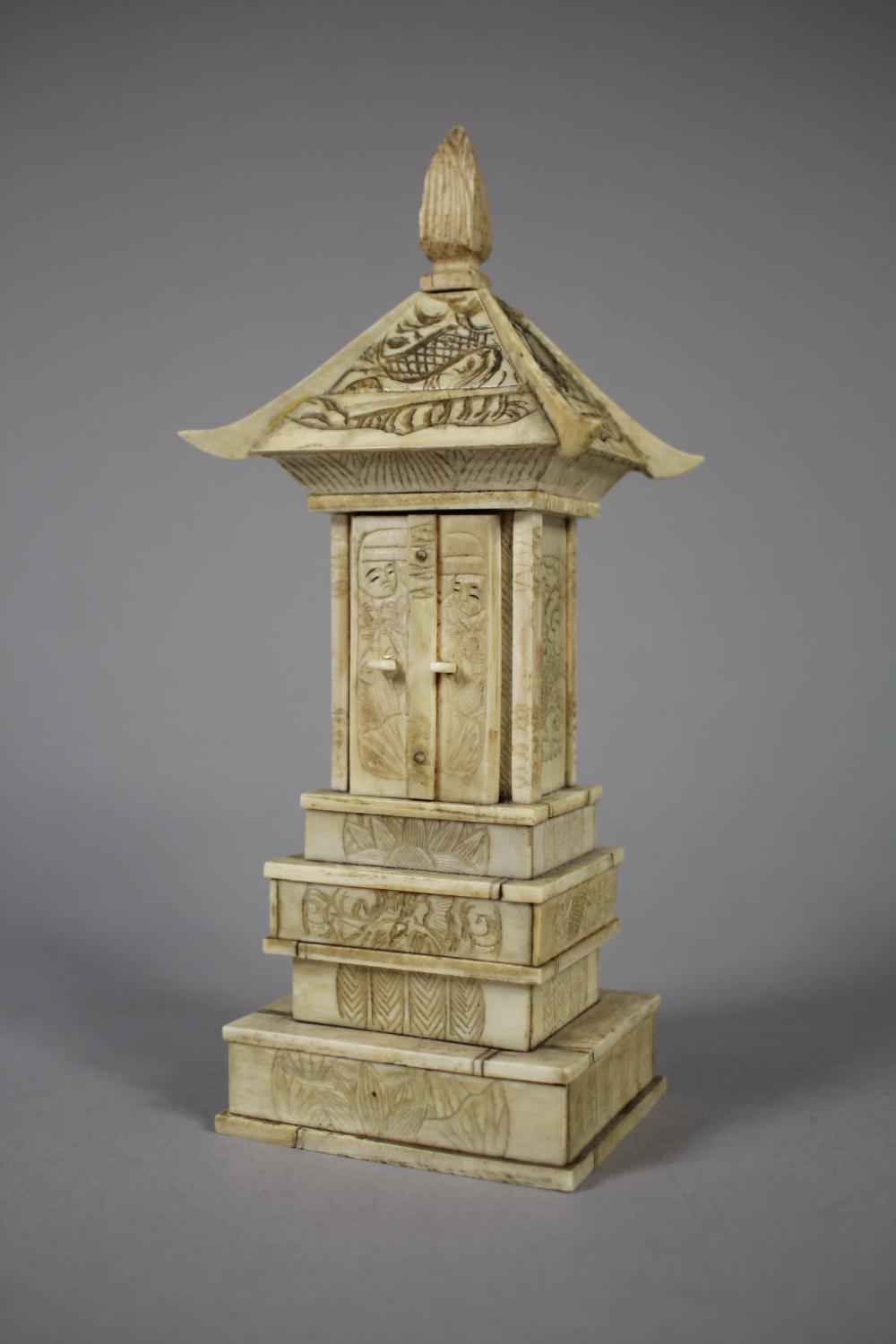 Japanese caved bone temple shrine, the doors open to show seated figure, approx 18cm H
