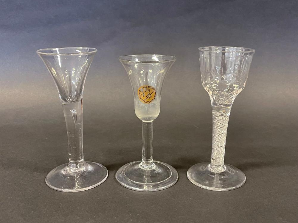 Three antique English Georgian wine glasses, one of trumpet shape with tear drop stem, air twist stem example, rare bell shaped bowl example, all with minor chips to foot rims, (3) 16cm x 15cm high