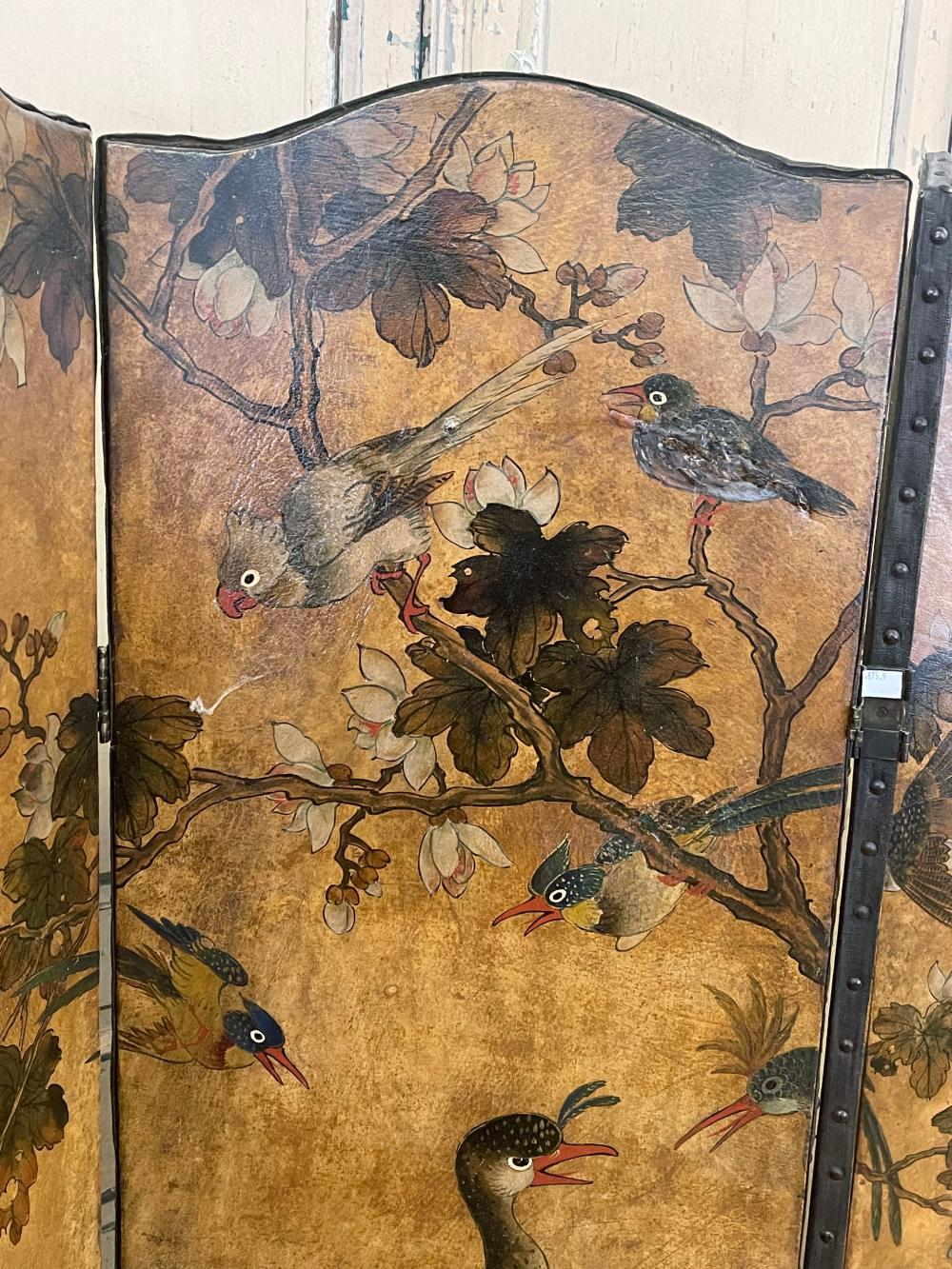 Antique four fold floor screen, painted leather and canvas backed, with studded trim, showing exotic colourful birds on blossoming branches, each panel approx 169cm H x 43.4 cm W
